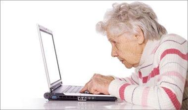 Äldre dam läser sin journal vid dator