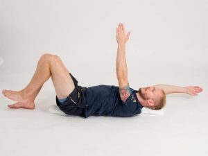 Bålkontroll i ryggliggande på handduk 4, slutpositition. Övning vid ryggskott, diskbråck, ischias och ont i rygg och bäcken.