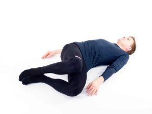 Ryggliggandes knäfällningar åt sidan. Övning vid ryggskott, diskbråck, ischias, lumbago och ont i ryggen