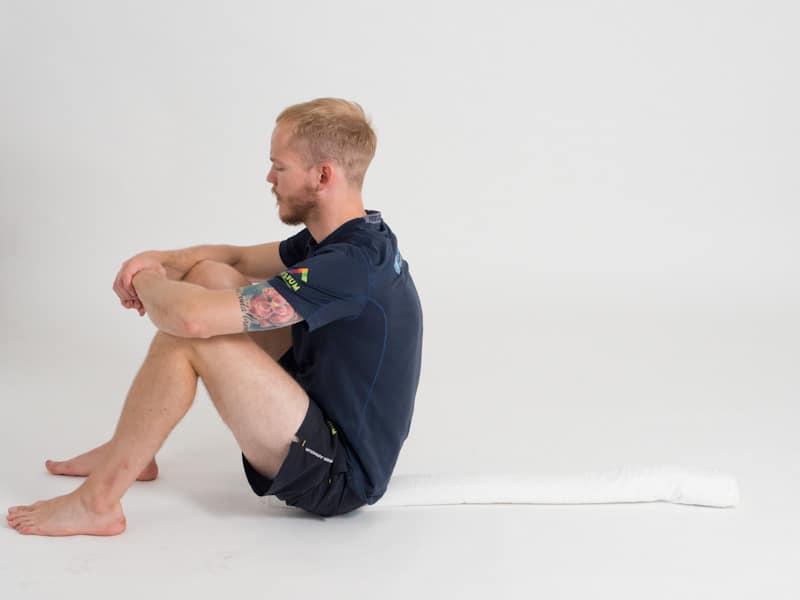 Bålkontroll i ryggliggande på handduk 1, startpositition. Övning vid ryggskott, diskbråck, ischias och ont i rygg och bäcken.