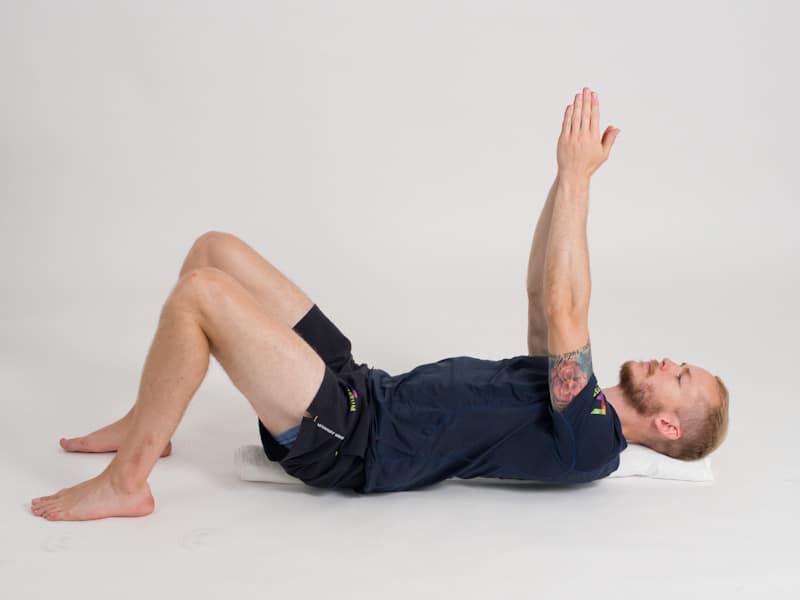 Bålkontroll i ryggliggande på handduk 2, startpositition. Övning vid ryggskott, diskbråck, ischias och ont i rygg och bäcken.