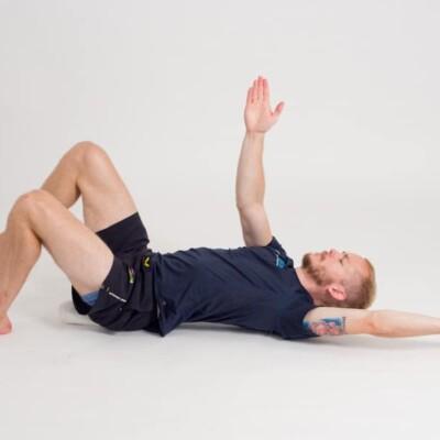 Bålkontroll i ryggliggande på handduk 3, slutpositition. Övning vid ryggskott, diskbråck, ischias och ont i rygg och bäcken.